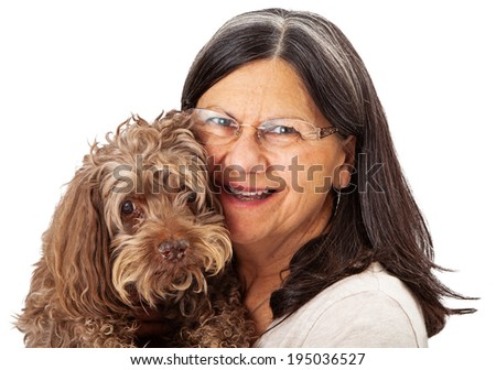 A happy and smiling woman with brunette and silver hair holding a senior mixed breed dog - stock photo
