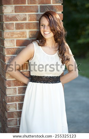 A happy and young brunette posing near a brick on a sunny day.  - stock photo