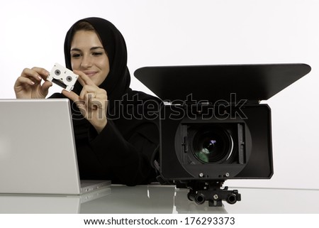 A Happy Arab Student Holding Her Show Reel In A Filming Studio - stock photo
