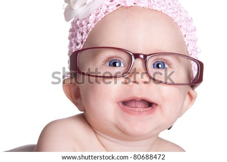A happy baby girl smiles with her glasses on.  She has a beautiful white bow on. - stock photo