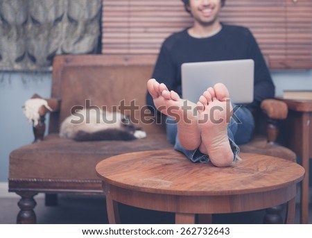 A happy barefoot man is resting his feet on a coffee table at home while working on his laptop, there is a cat sleeping next to him - stock photo