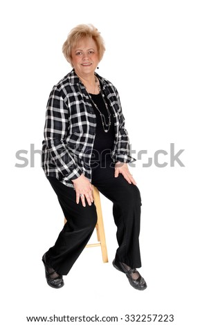 A happy blond mature woman sitting on a chair, looking into the camera, isolated for white background.  - stock photo