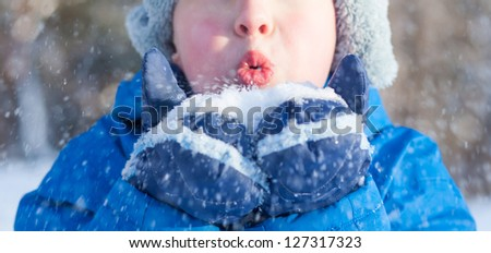 A happy boy is playing with snow on winter - stock photo