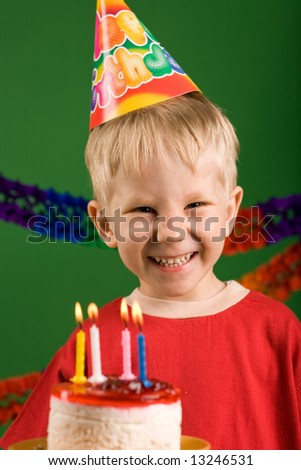 A happy boy on his birthday, making a wish - stock photo