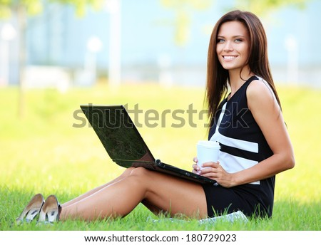 A happy business woman working on her laptop outside in the park  - stock photo