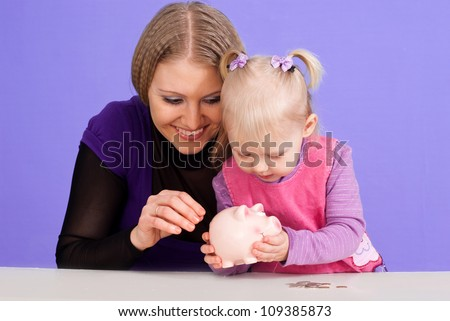 A happy Caucasian mother with her daughter play with the piggy bank on a violet background - stock photo
