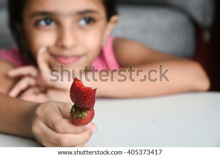 A happy, cheerful, laughing child/ kid/ young girl enjoying her tasty sweet ice cream cone on summer vacation/ holiday Kerala, India, Asia. Indian daughter playful looking at her lollipop and smiling. - stock photo