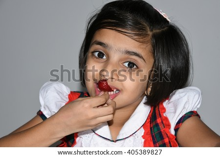 A happy,cheerful, laughing child/ kid/ young girl holding strawberry and licking with tongue Kerala, India, Asia. Indian daughter playful enjoying her tasty/ delicious fruit salad and smiling. - stock photo