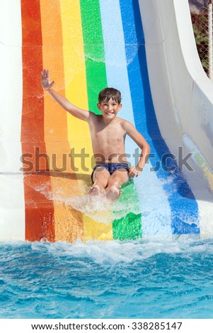 A happy child is sliding on water slide in aquapark - stock photo