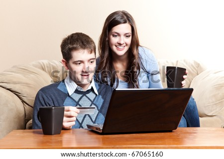 A happy couple holding a credit card shopping online - stock photo