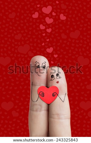 A happy couple in love with painted smiley and hugging  Finger art. Lovers is embracing and holding red heart. There are path included in image. You can easily cut out fingers from the background.  - stock photo