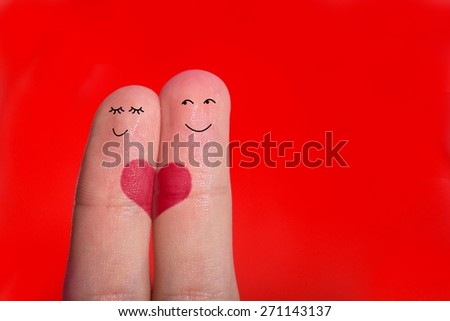 A happy couple in love with painted smiley on the red background - stock photo