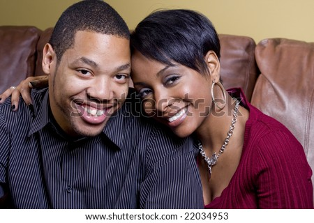 A happy couple on the couch and the woman has her arm around the man - stock photo