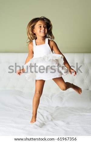 A happy cute young girl in white dress having fun jumping on bed - stock photo