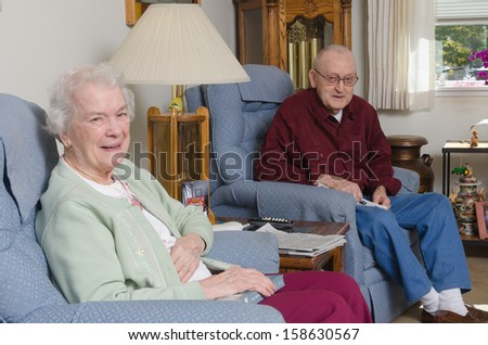A happy elderly welcomes the viewer to their home. - stock photo