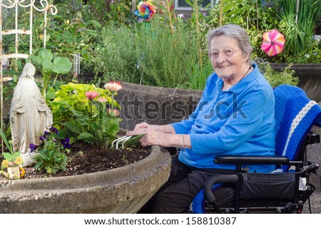 A happy elderly woman in an assisted-living facility tends to her flowers in a wheelchair-accessible garden container. - stock photo