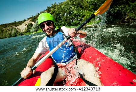 A happy entusiastic male in red inflatable canoe having a fun ride in calm waters of a river. - stock photo