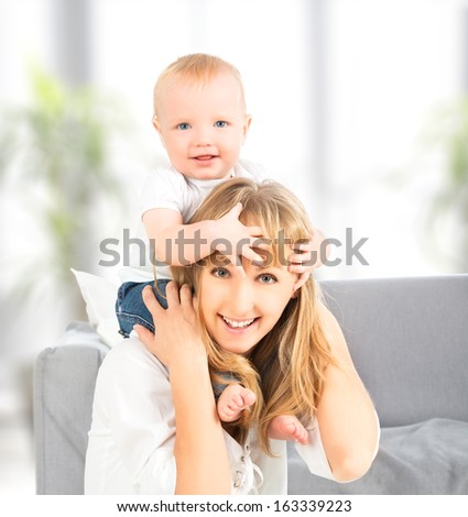 A happy family. baby sits astride the shoulders of the mother - stock photo