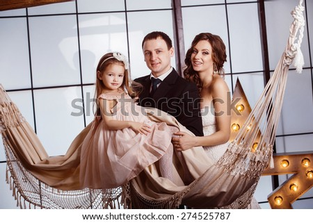 A happy family concept. Beautiful pregnant wife in wedding dress,  her cute daughter and young father are standing near a hammock at a window background. - stock photo