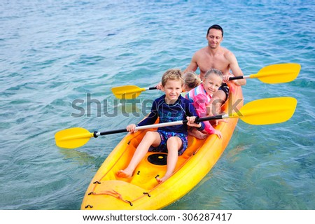 A happy family: dad and his children- a boy and two girls kayaking in the blue waters of the ocean - stock photo
