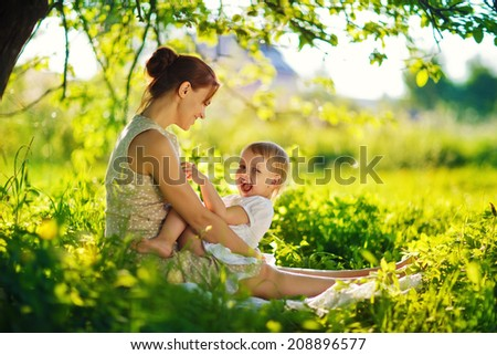 A happy family having a picnic in the green garden in a sunny spring day: a beautiful smiling mother sitting on green grass and her little laughing daughter on her legs - stock photo