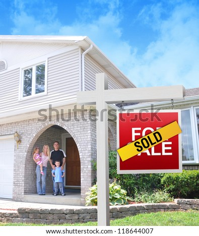 A happy family is standing in front of a home with a For sale sign with a sold sticker on top. There is an exterior image of the hose with clouds in the background. - stock photo