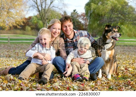 A happy family of four people, including mother, father, young child, and toddler brother are sitting outside in the fallen maple leaves with their pet German Shepherd dog on an Autumn day. - stock photo