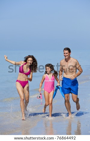 A happy family of mother, father and child, a daughter, running holding hands and having fun in the waves of a sunny beach - stock photo