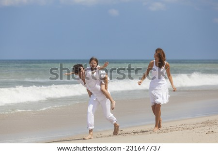 A happy family of mother, father and one child, a daughter, running playing piggy back and having fun in the sand of a sunny tropical beach - stock photo