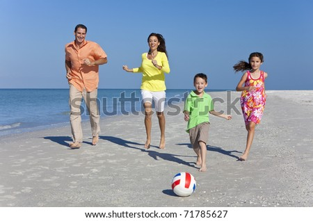 A happy family of mother, father and two children, son and daughter, running kicking a football and having fun in the sand of a sunny beach - stock photo