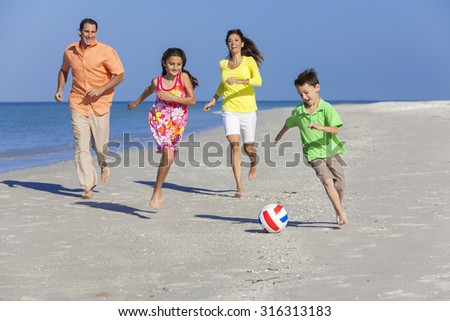 A happy family of mother, father and two children, son and daughter, running playing soccer or football in the sand of a sunny beach - stock photo