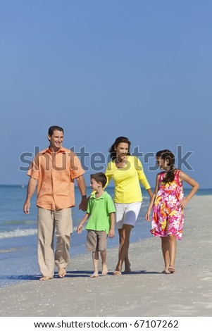 A happy family of mother, father and two children, son and daughter, walking and having fun in the sand of a sunny beach - stock photo