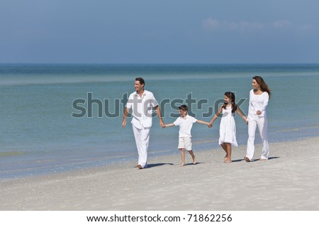 A happy family of mother, father and two children, son and daughter, walking and holding hands on a sunny tropical beach - stock photo