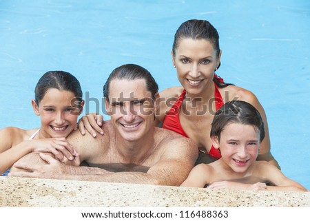 A happy family of mother, father, son & daughter, parents & children, boy & girl, having fun playing in a swimming pool - stock photo
