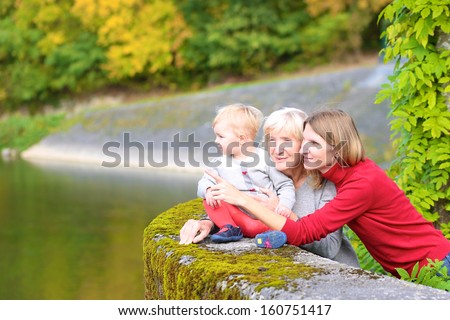 A happy family of three generations, mother, daughter, grandmother and little baby granddaughter, are standing together on the bridge of the river with the colorful trees around - stock photo