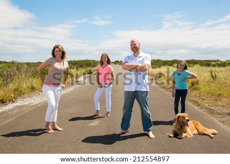 A happy family pose for a photo on a quiet road in the country - stock photo
