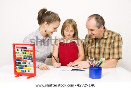 A happy family sitting together. the parents are helping their little daughter with the homework against white wall - some educational tools and objects on the table. - stock photo