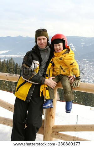a happy father and small son in the ski resort  - stock photo