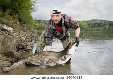 A happy fisherman presenting his fishing trophy caught in a Polish lake - catfish (Silurus glanis) - stock photo