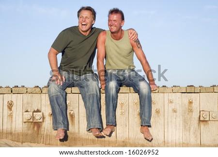 A happy gay couple having fun on the beach. - stock photo