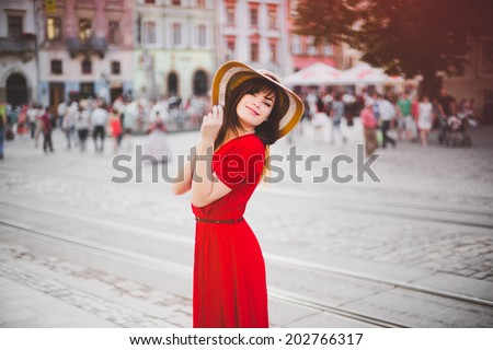 a happy girl in a red dress and widebrimmed hat in the city-center - stock photo