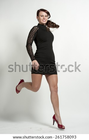 A happy girl jumping on a white background in a studio. - stock photo