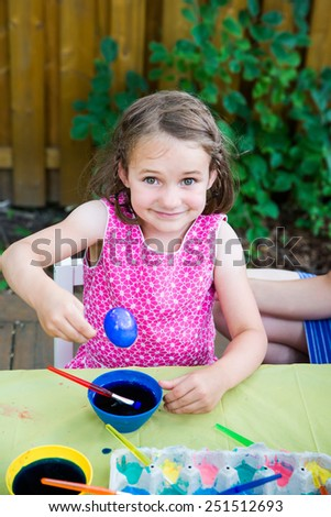 A happy girl sits outside in a springtime garden setting at a crafts table painting and decorating Easter eggs.  she smiles proudly and holds up a freshly colored blue dyed egg.   Part of a series. - stock photo