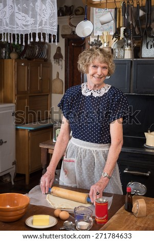 A happy grandmother making a pie  dressed in vintage clothing in a kitchen from 1940 - stock photo