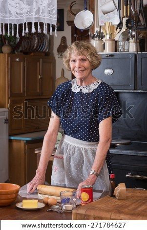 A happy grandmother making a pie in clothing and kitchen in the 1940's - stock photo