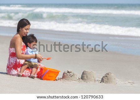 A happy hispanic mother and young child boy son having fun in the sand together making sand castles on a sunny beach - stock photo
