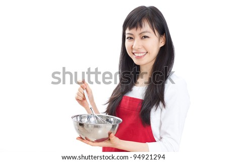 A happy housewife holding a bowl and whisk - stock photo