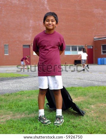 A happy Indian school kid smiling in front of the classroom - stock photo