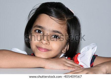 A happy, joyful, dreamy, cheerful, laughing child/ kid/ young girl Kerala, India, Asia. Indian daughter playful, naughty, smiling. - stock photo
