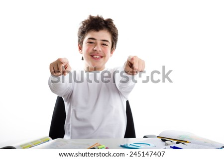 A happy Latin boy is sitting while doing homework: he is happy and smiles pointing his index fingers to viewers - stock photo